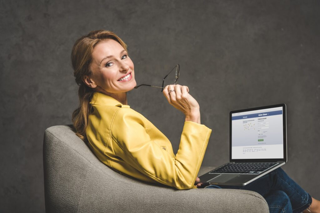 smiling mature woman using laptop with facebook website and sitting in armchair