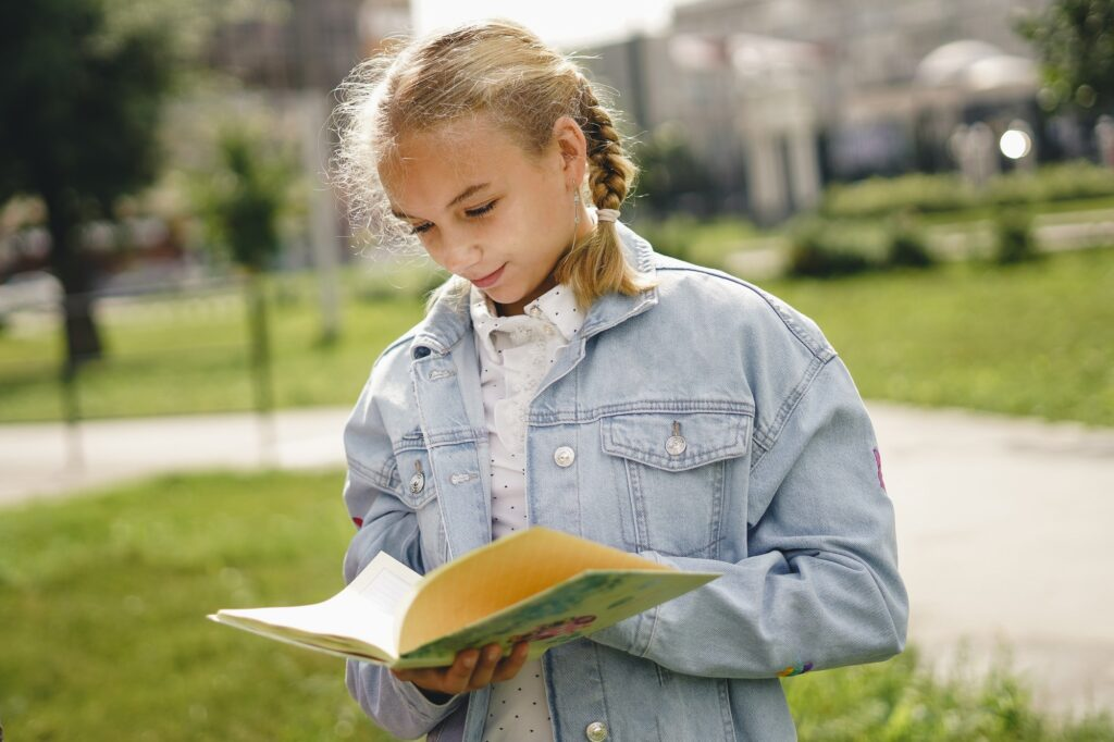 Young school girl with school diary outdoor