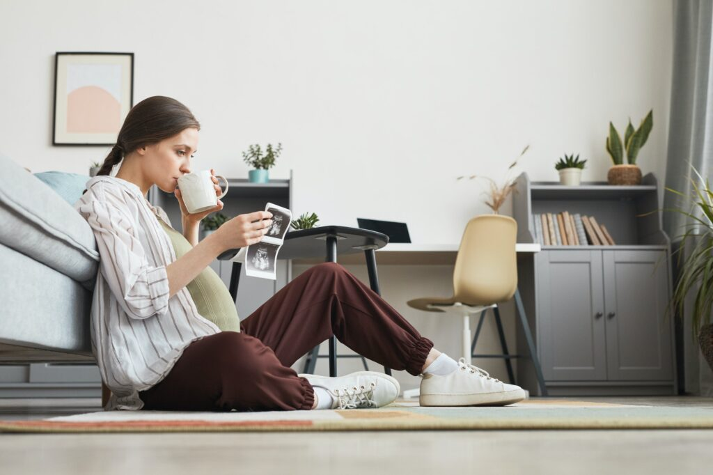 A person sitting on the floor and drinking from a cup