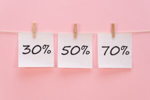 sticker with 30% 50% 70% percent % icon hangs with a clothespin on a rope on a pink background